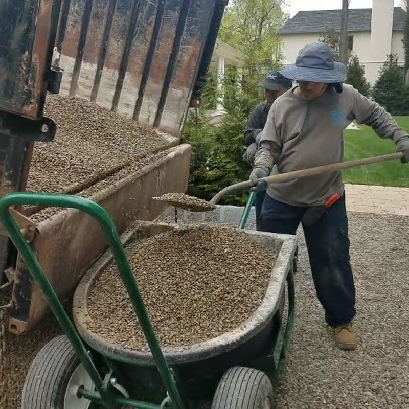 Man shoveling gravel from dump truck into The Landscaper's Buddy's tub attachment for hauling up to 2,100 lbs of granules.