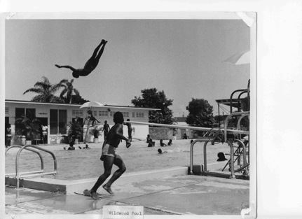 A vintage, black and white photo of African Americans playing in a public swimming pool