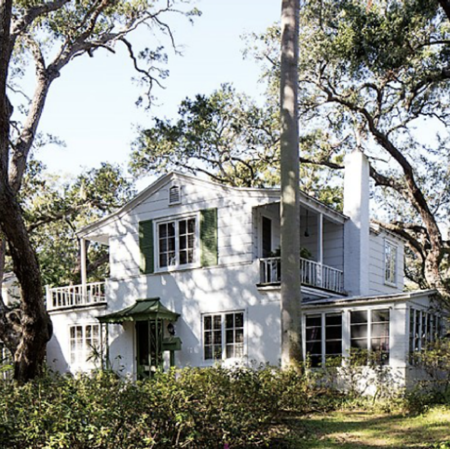 Historic white cottage surrounded by greenery.
