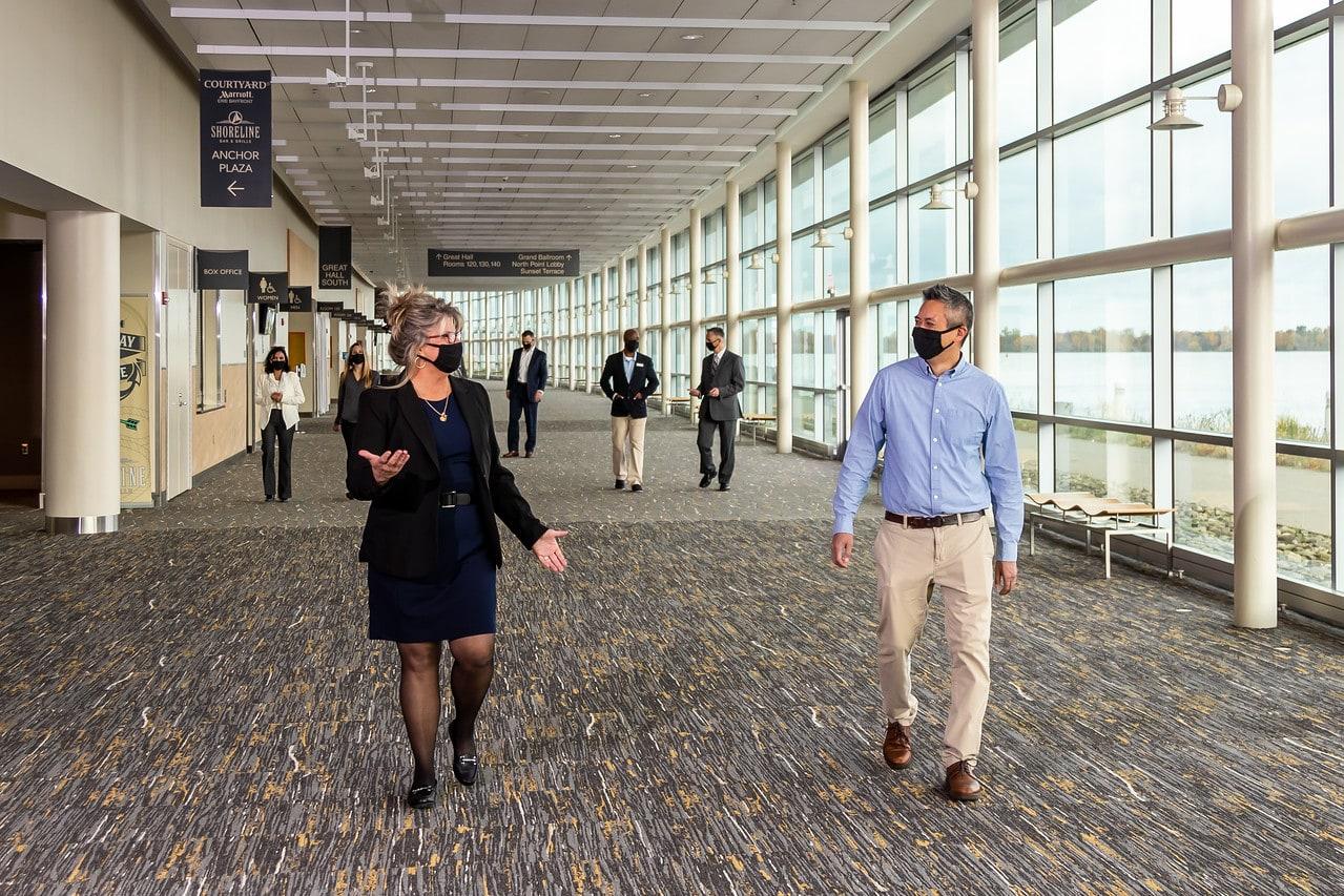 Meeting attendees wearing masks walking 6 feet apart down a long hallway overlooking Lake Erie