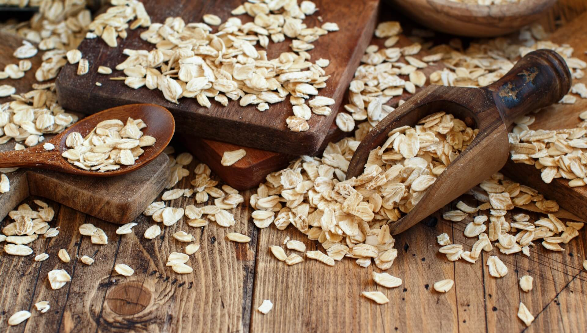 Oats and scoop on a wooden countertop
