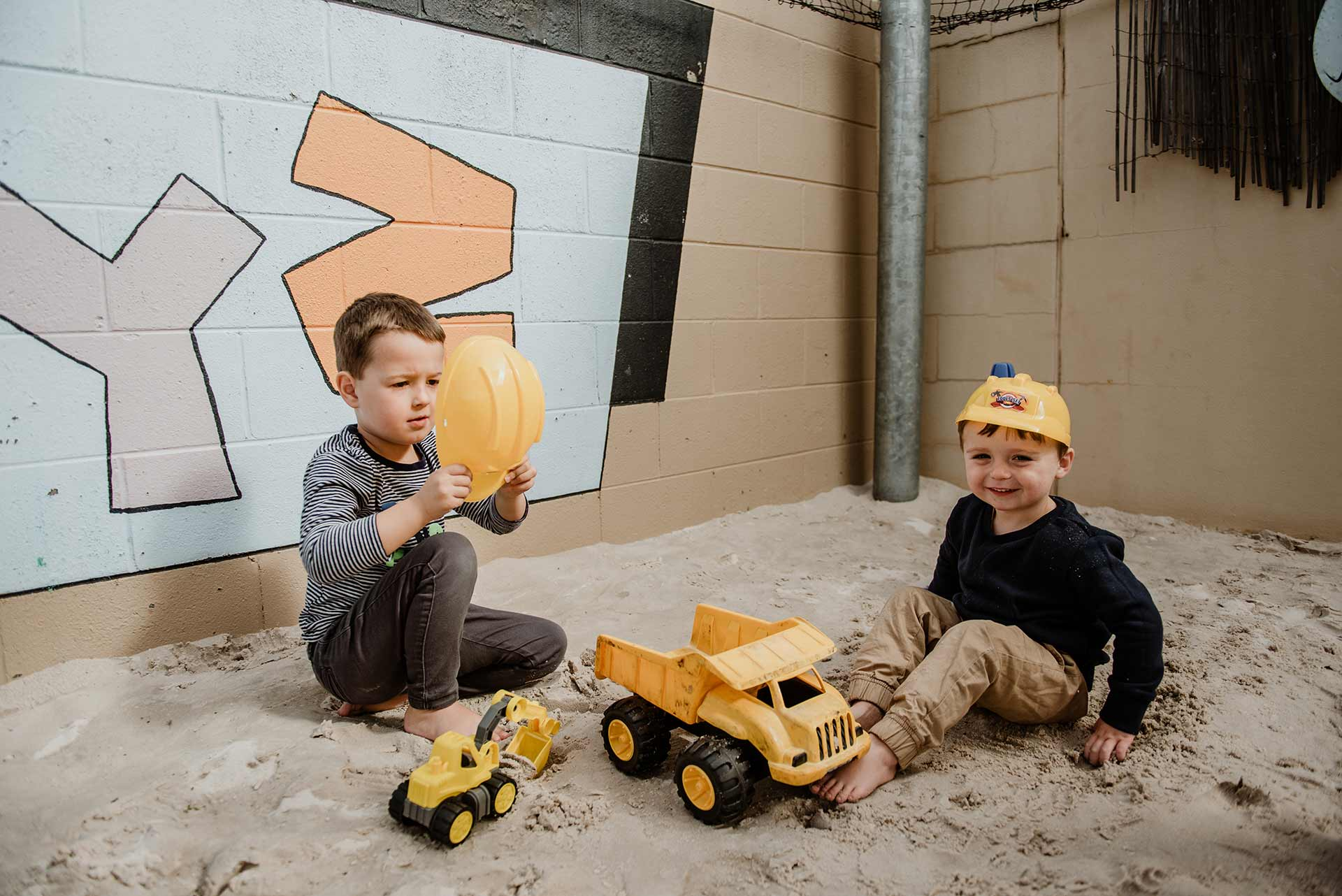 Children playing toy truck in sand at Centrepoint child centre