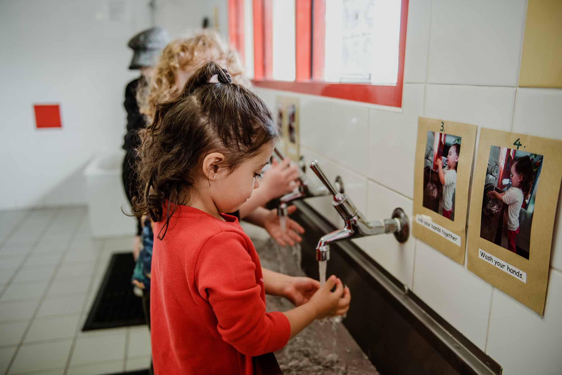 Children washing their hands together at Centrepoint childcare centre
