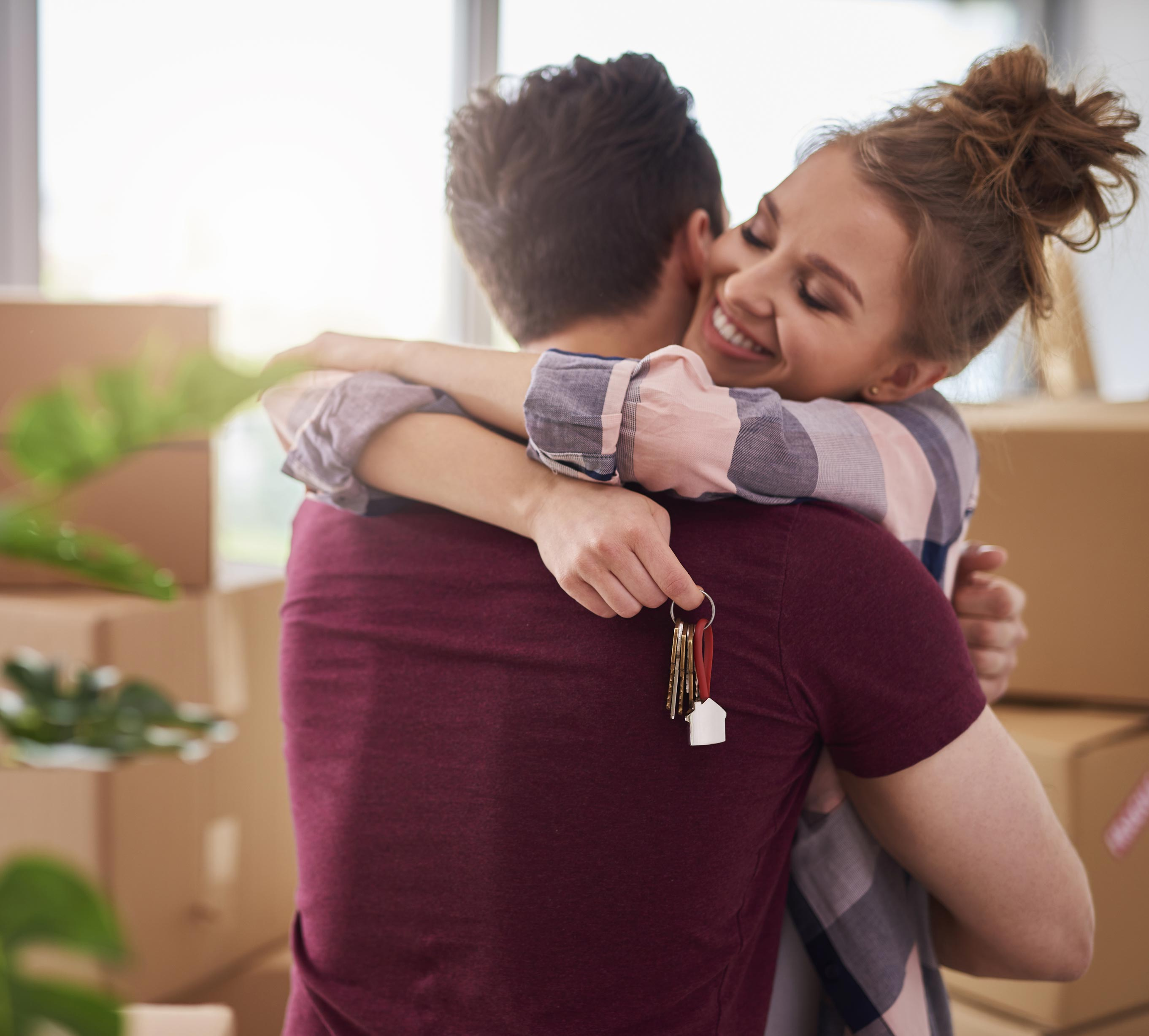 Man and woman hugging and holding new house keys