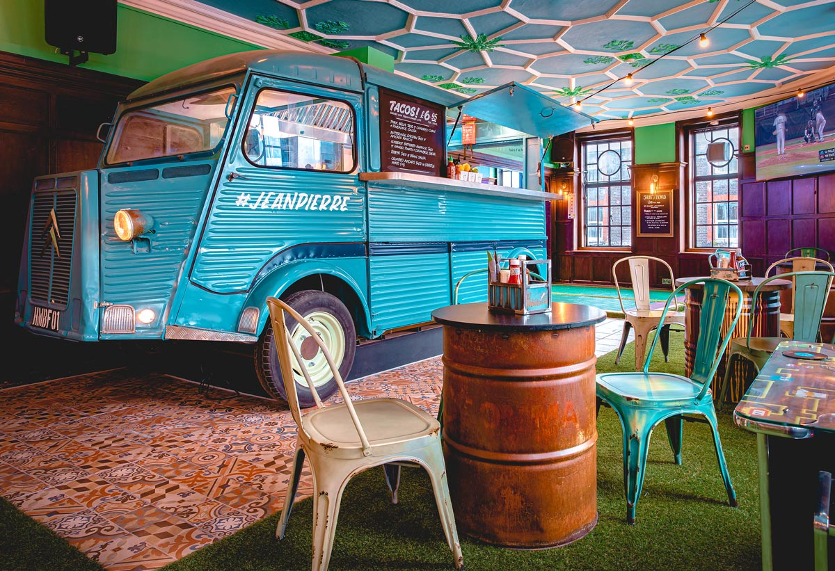 Ram Inn, Wandsworth food truck inside the pub, with steel barrel tables in the forground.