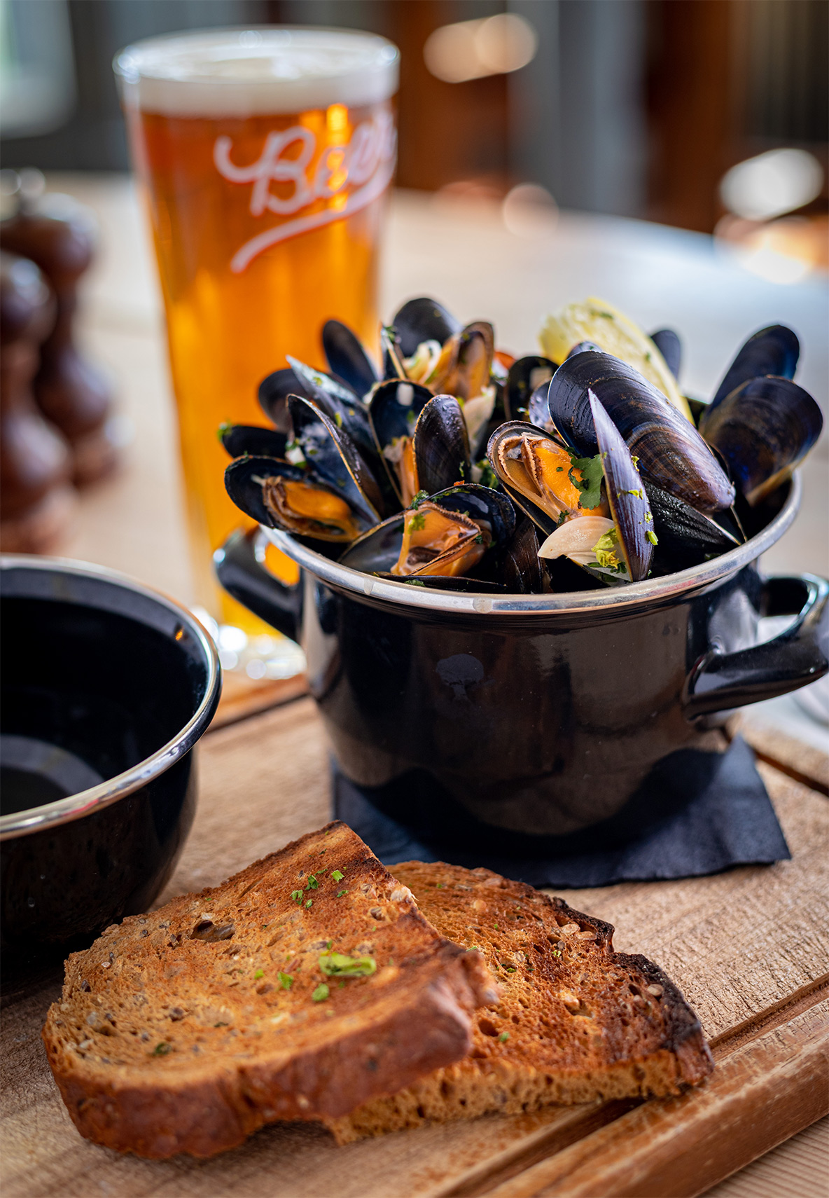 Food Photography. Muscles on a wooden cutting board with a pint a larger in the background. Rich colours with real pub atmosphere.