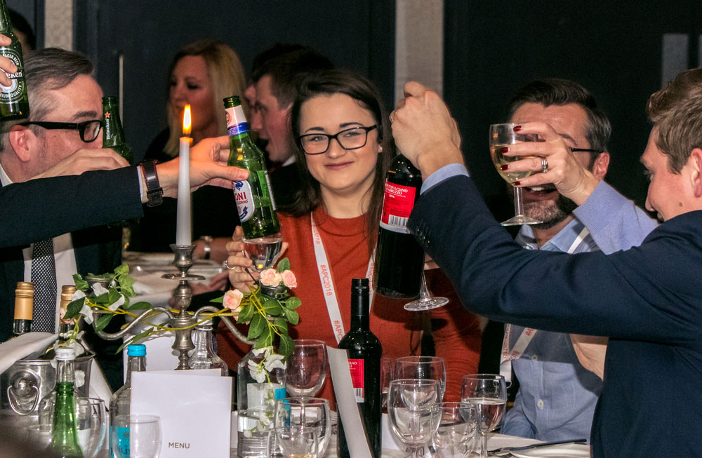 Evening dinner with table toasting. Smiling female of the group is in focus behind raised glasses