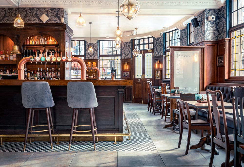 The Ram Inn, Wandsworth interior photograph. Light shimmers in from the right over the deep wood surfaces.