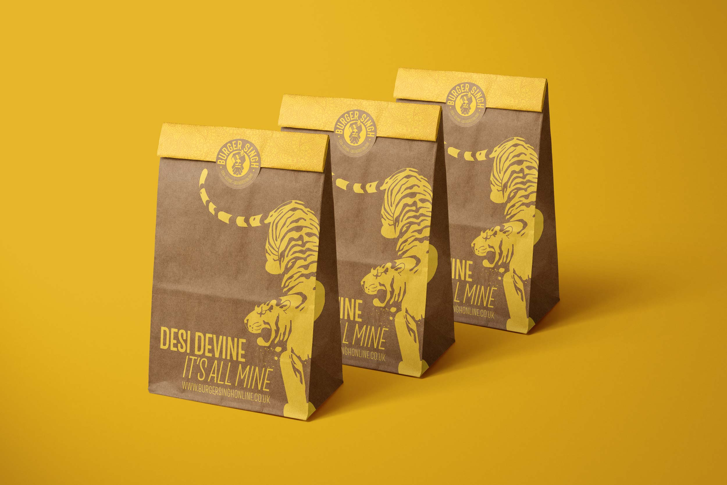 Burger Singh take-away bags with tiger illustration and logo. Heading Desi Divine, It's all mine.