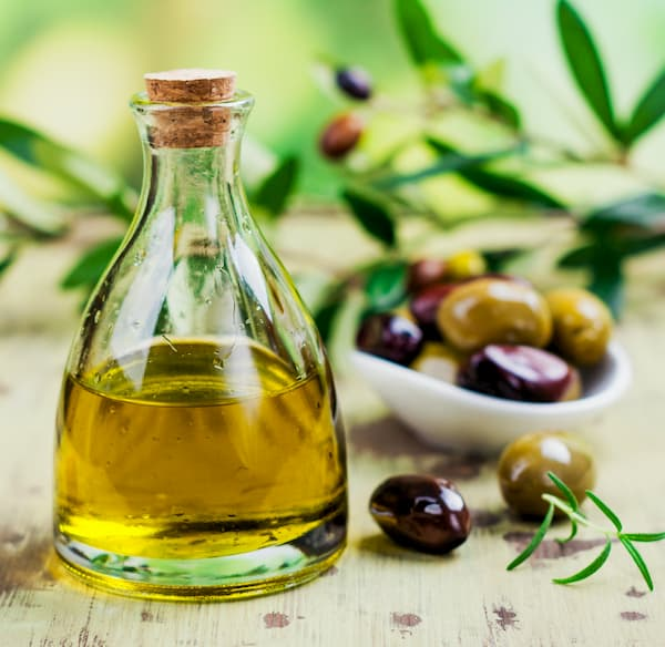 Flacon d'huile d'olive avec des olives entières à coté (photo)