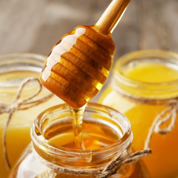 Cuillère à miel sortant d'un pot de miel (photo)