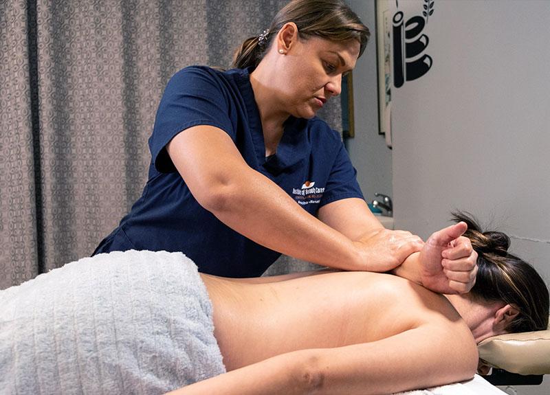 Estudiante del curso Masaje Terapeútico practicando masaje de espalda