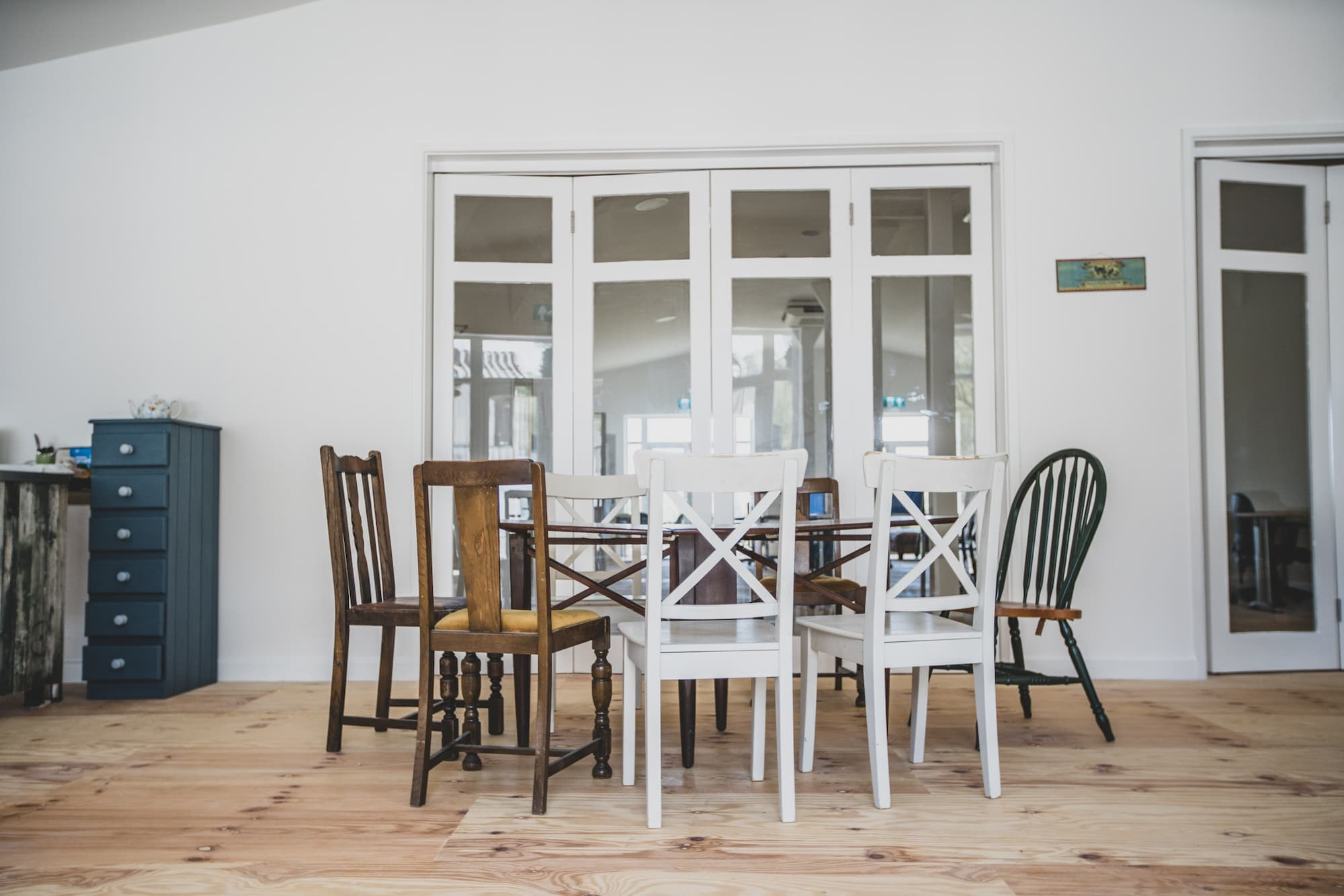 A table surrounded by chairs in a light room with wooden floors and white walls.