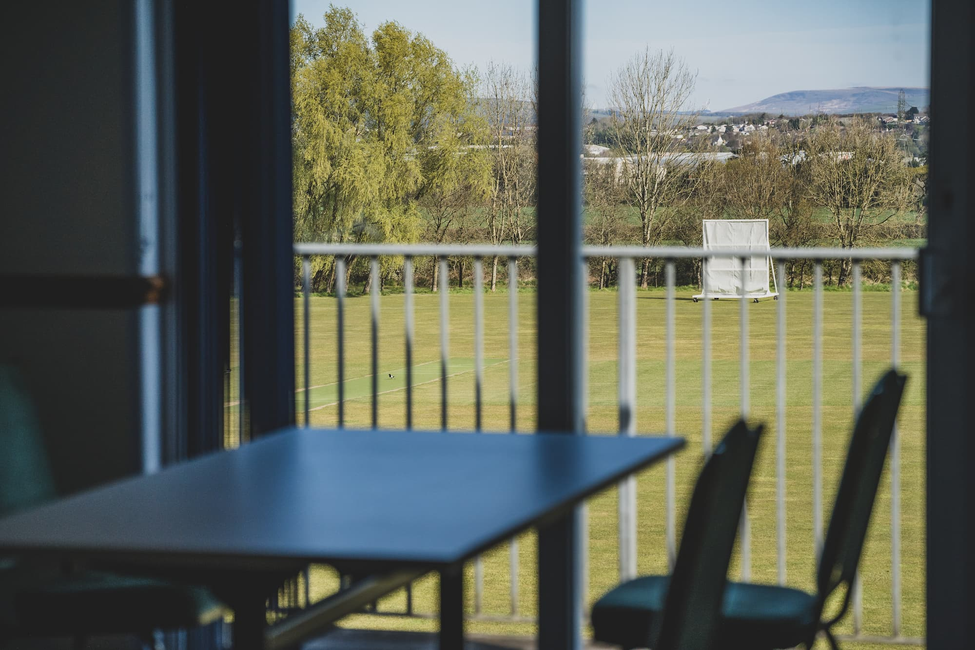 A table and set of chairs next to an upstairs window overlooking the cricket field.