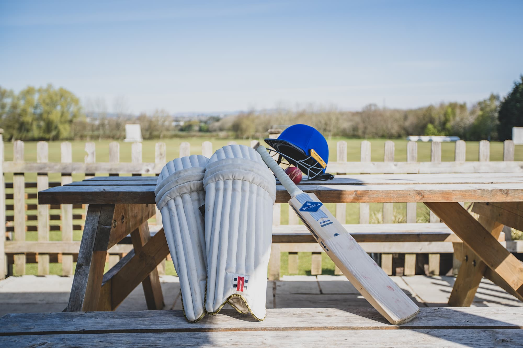A cricket bat, helmet and shin pads on a picnic bench outside the clubhouse.