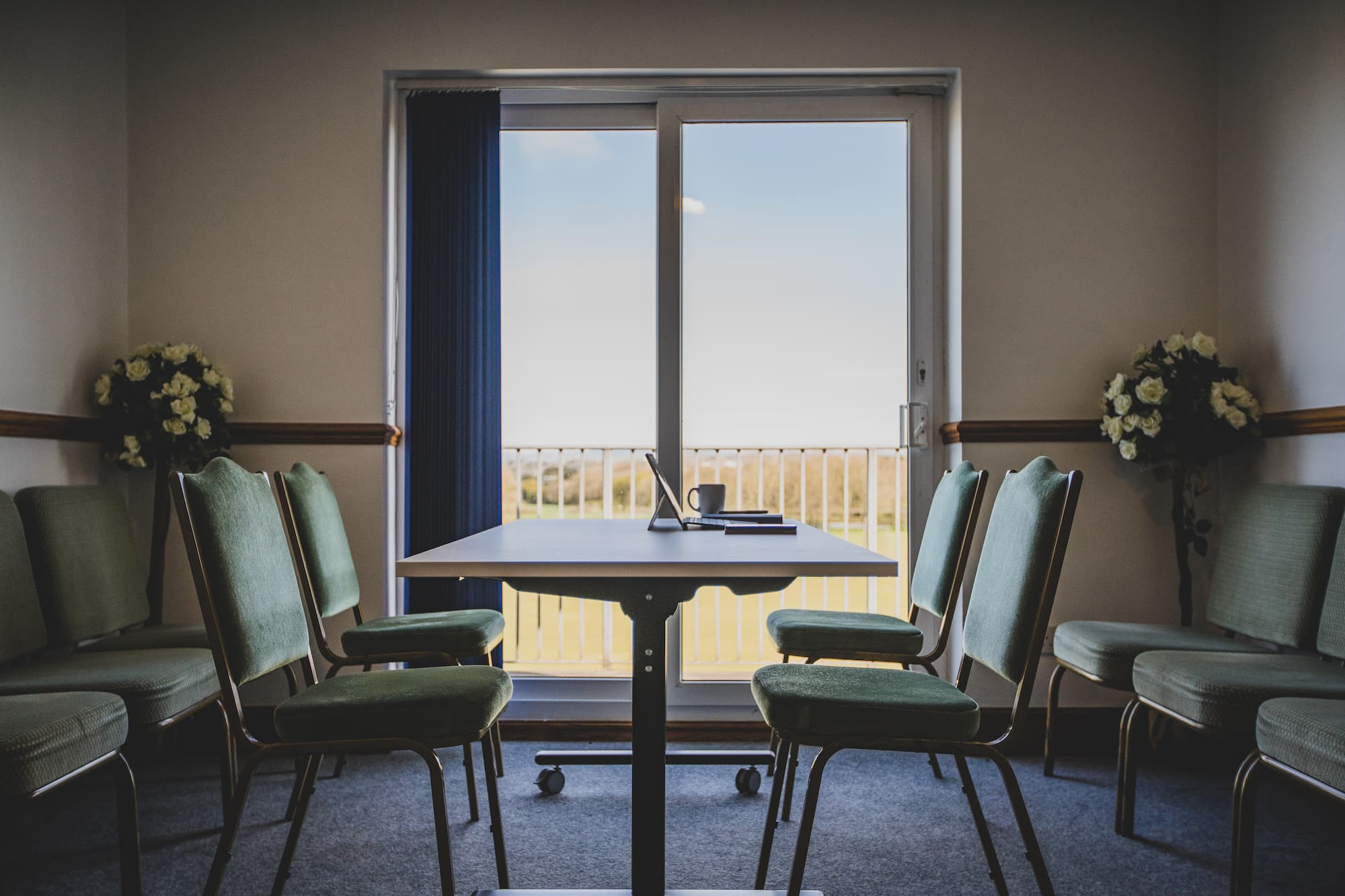 A table and four chairs in front of a window overlooking the grounds.