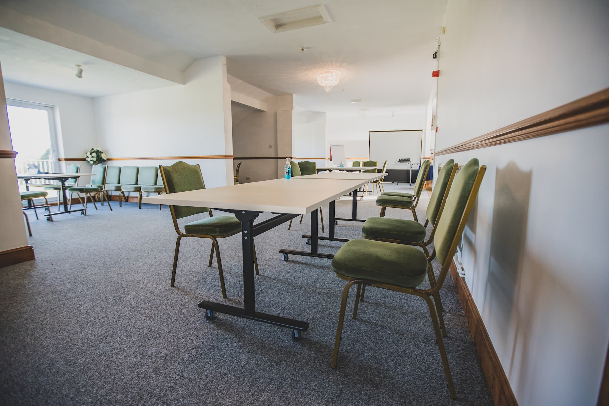 A large, light room for working in with plenty of tables and chairs spaced out.