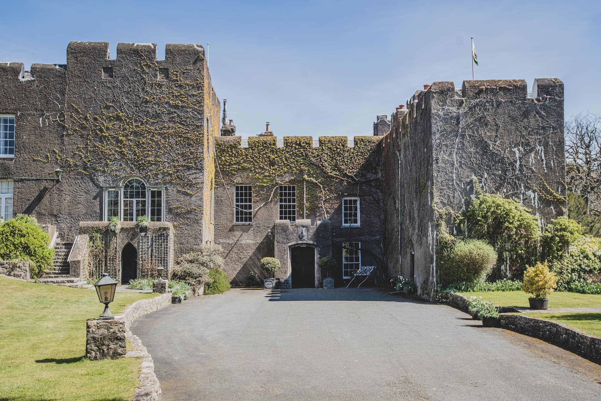 The front of the castle partly covered in climbing plants. There is a green lawn in front and a wide driveway.