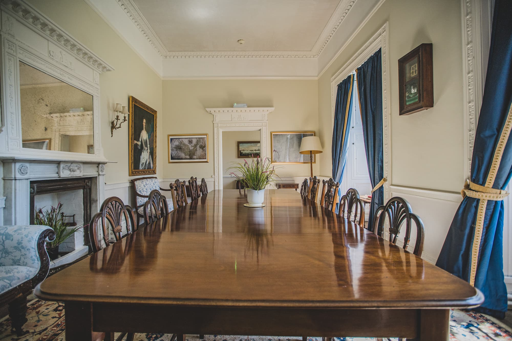 A large table with chairs for several people in a long room with a large fireplace and two tall windows.