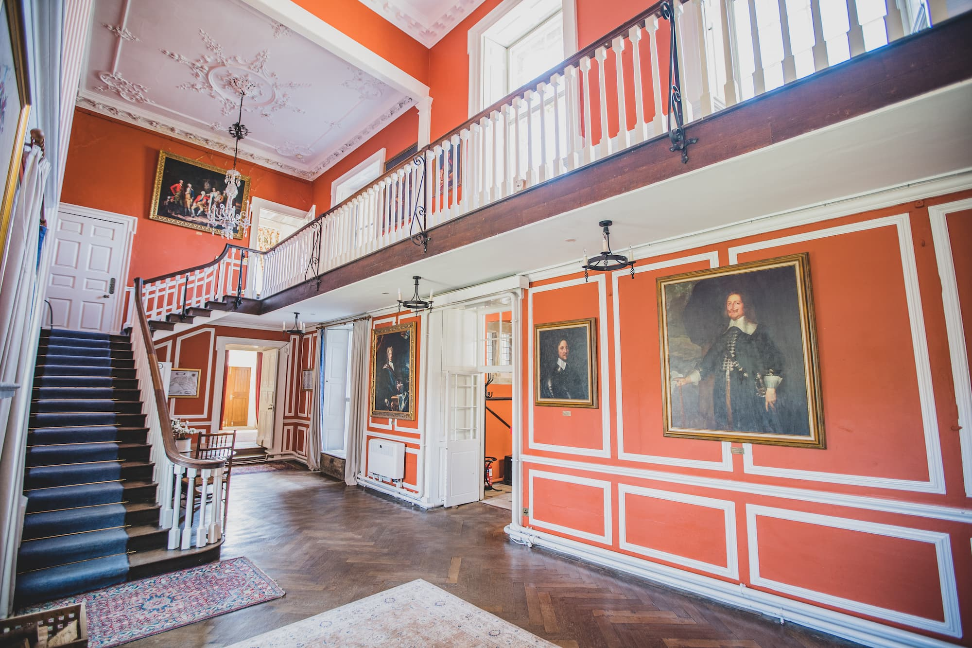 The foyer of the castle with a grand staircase, tall ceilings and painted portraits on the walls.