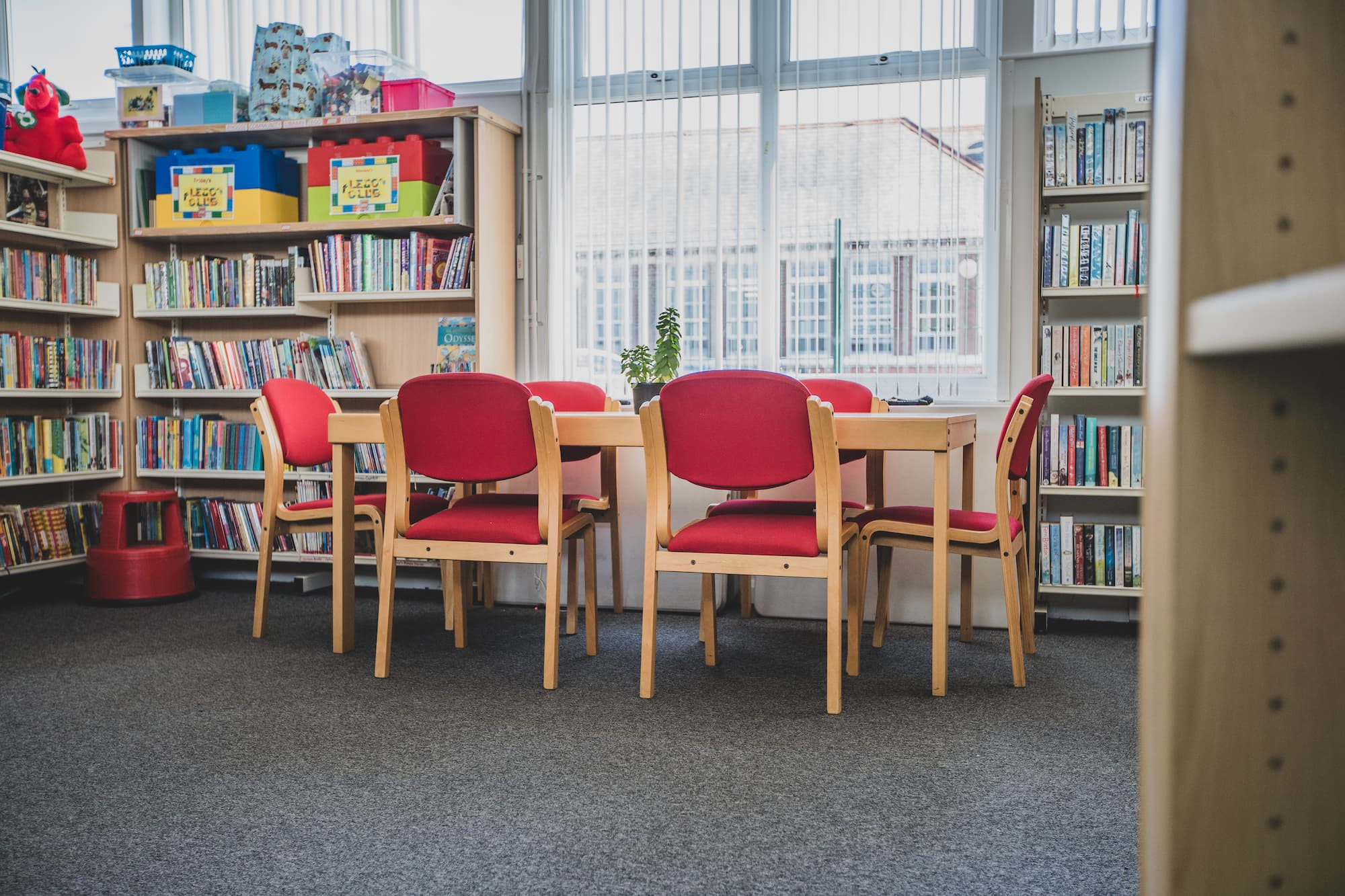 A table with six chairs around it next to a tall window and surrounded by book cases.