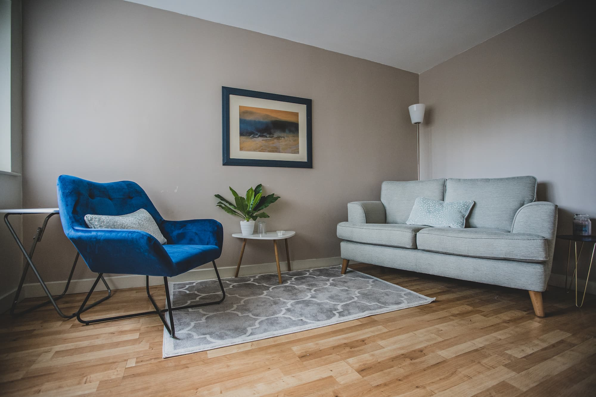 A casual space with a grey sofa, blue armchair and two side tables.