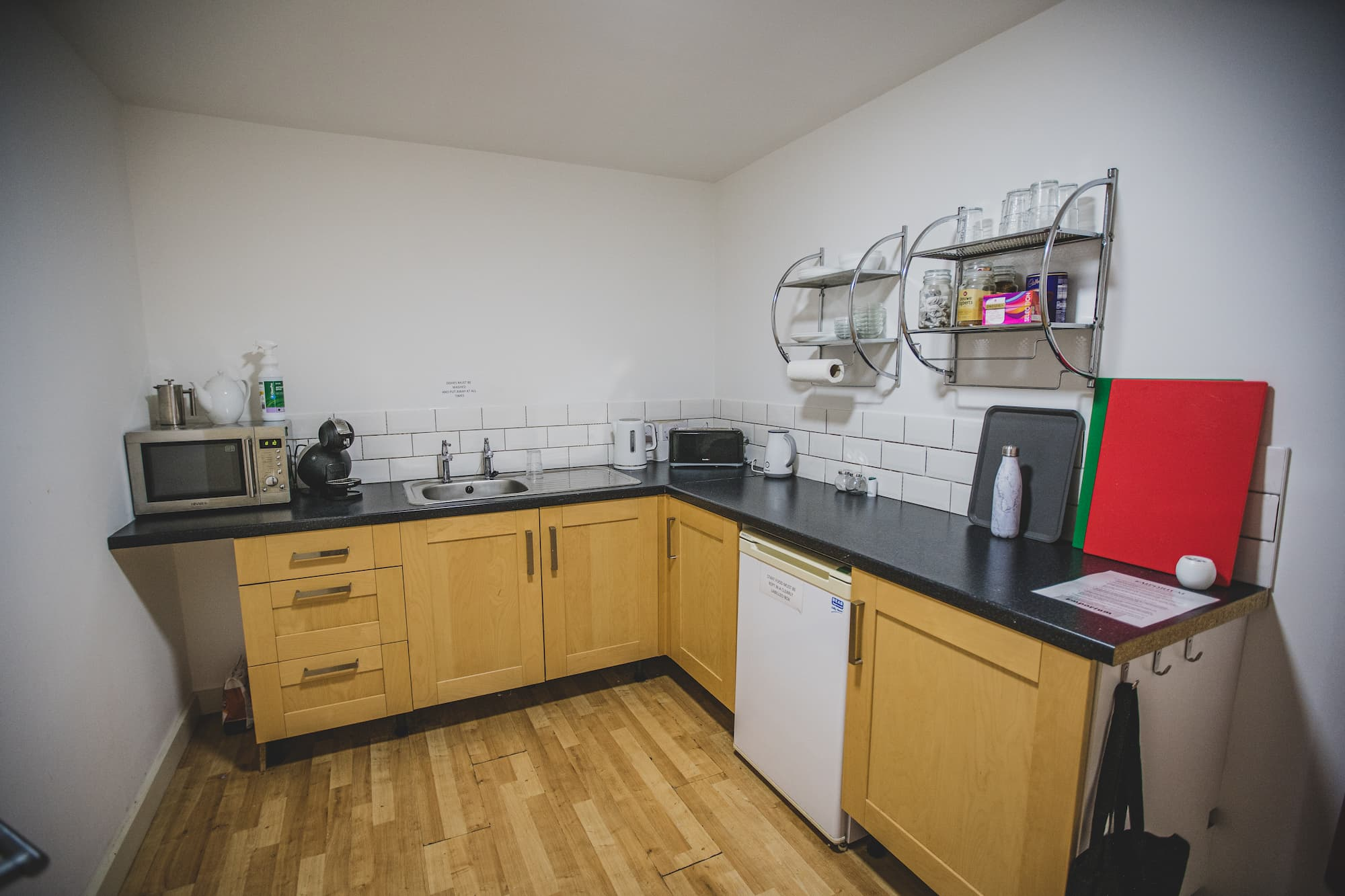 A corner kitchen with a sink, worktop space, a fridge and a microwave.