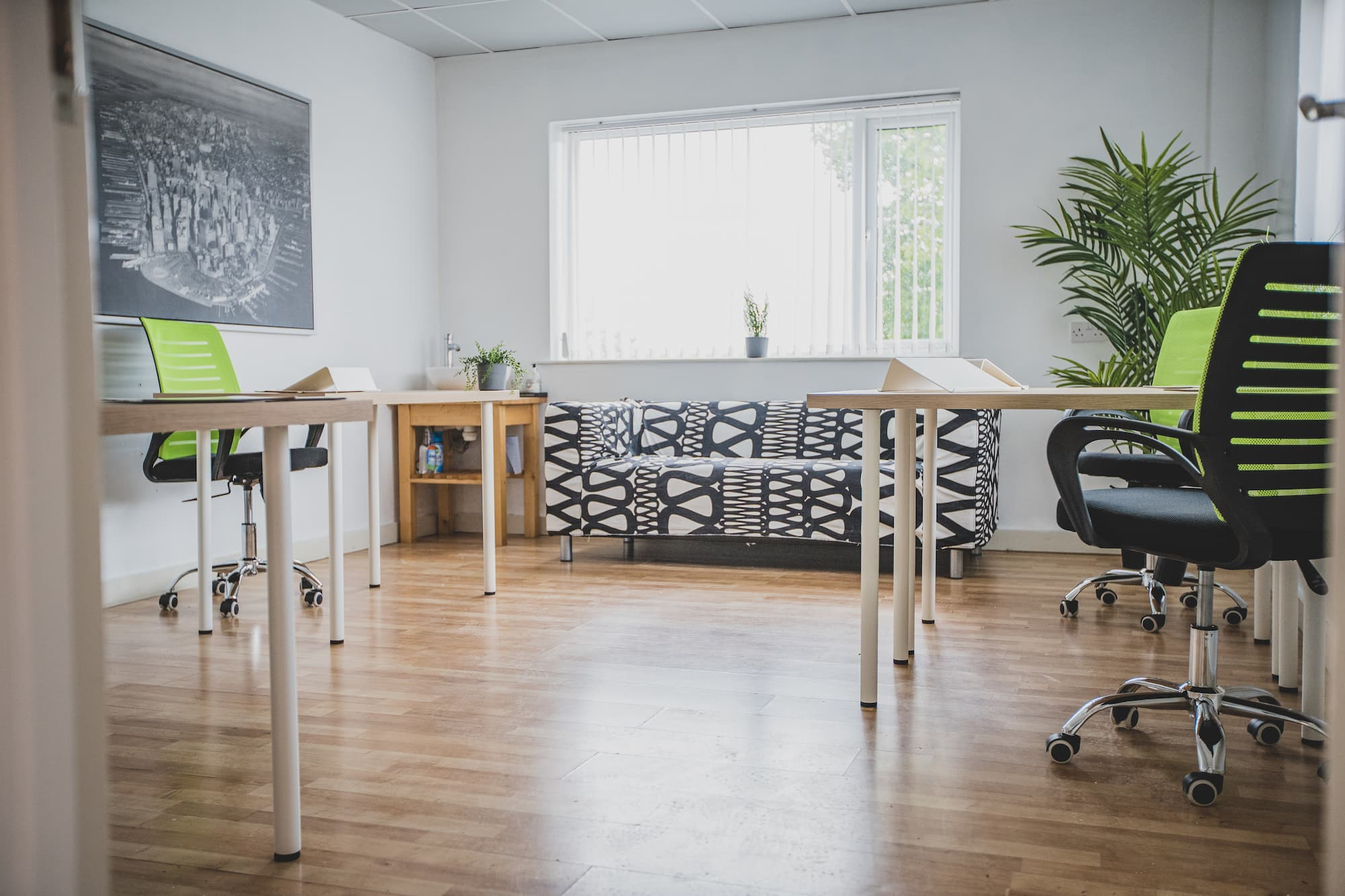 A workspace with a sofa and three work desks with swivel chairs.