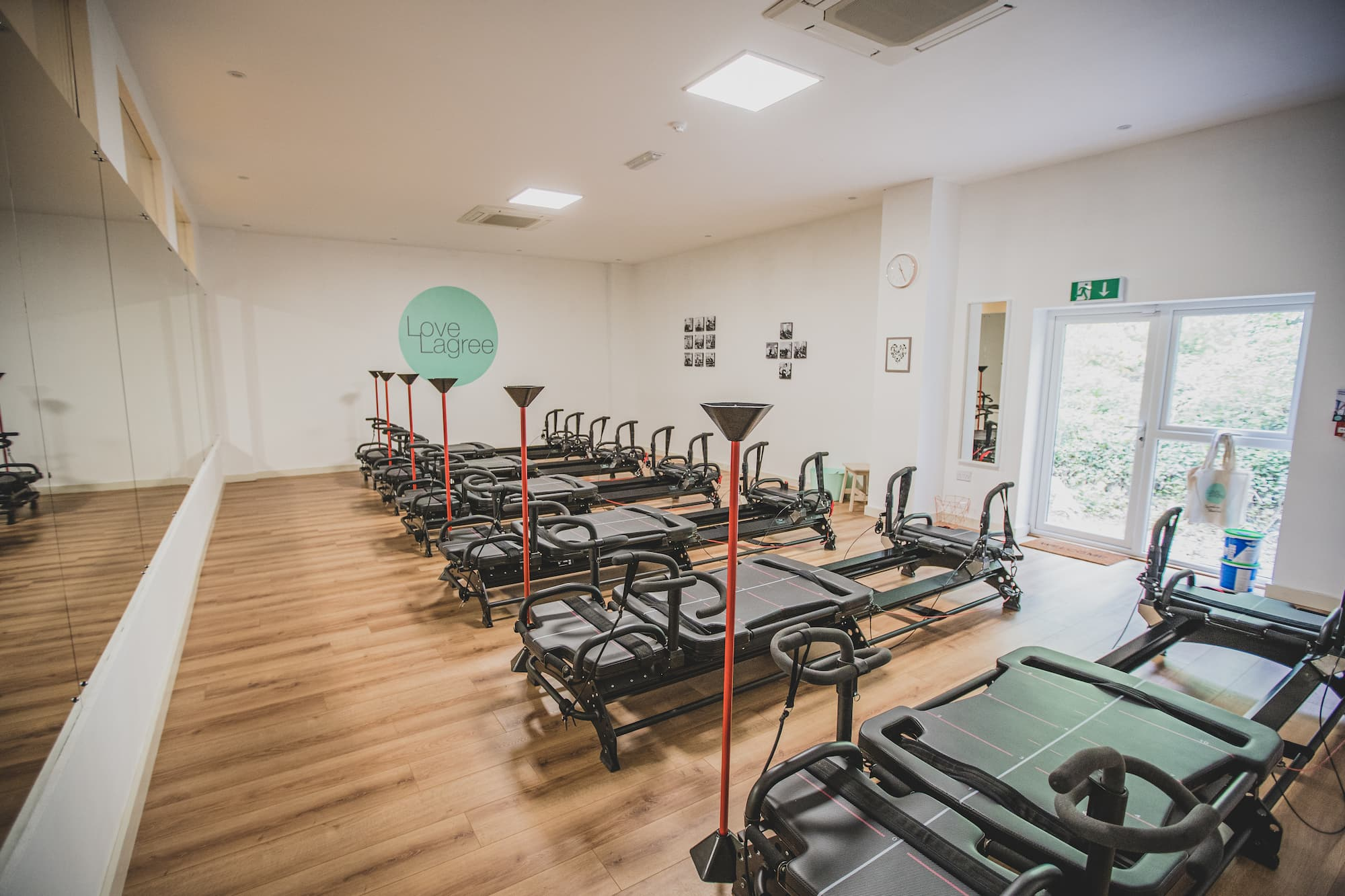 A large gym room, with equipment and a mirror spanning the width of the wall.