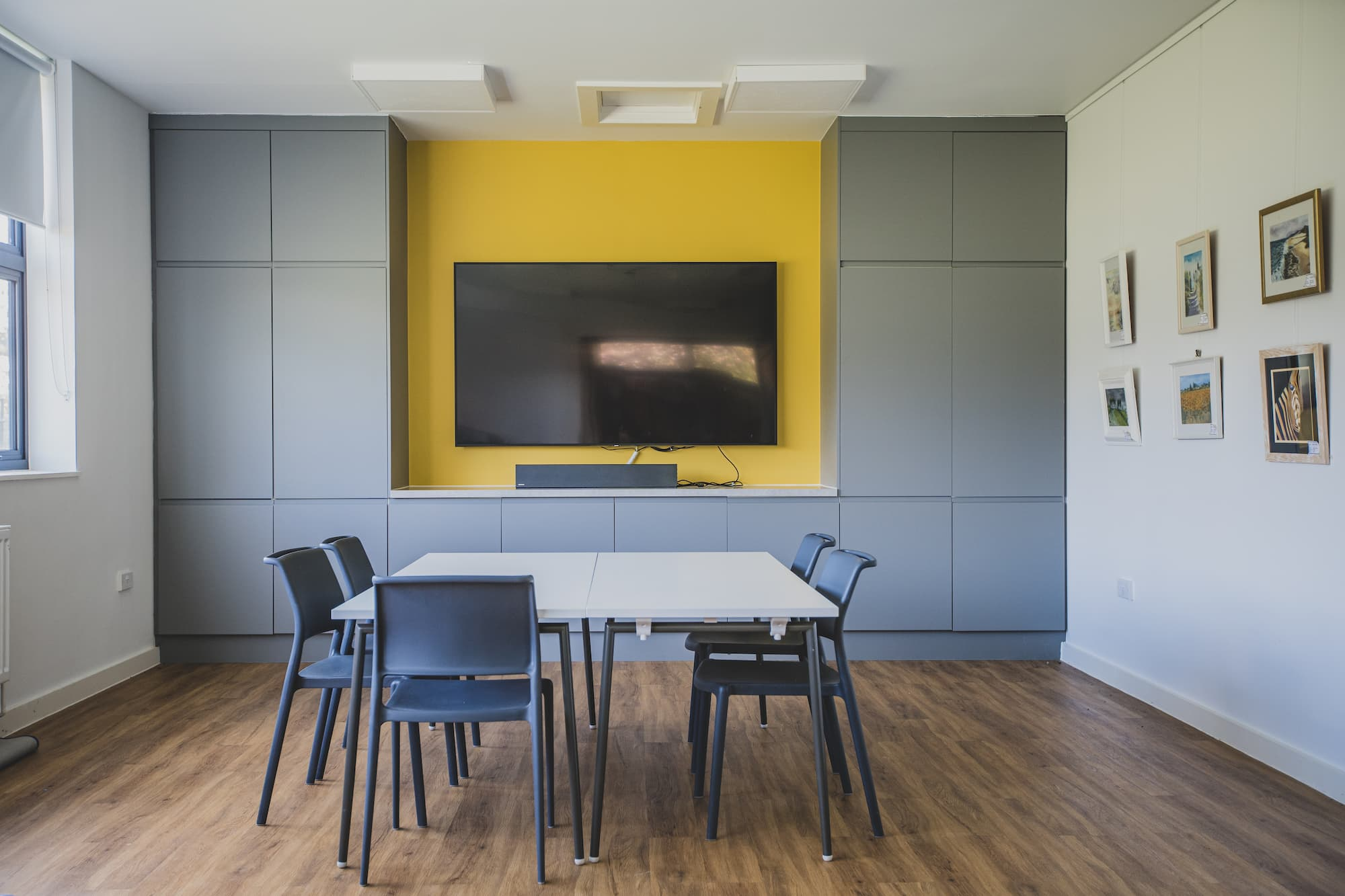 A meeting room with a large, wall mounted monitor and a table with room for eight chairs.