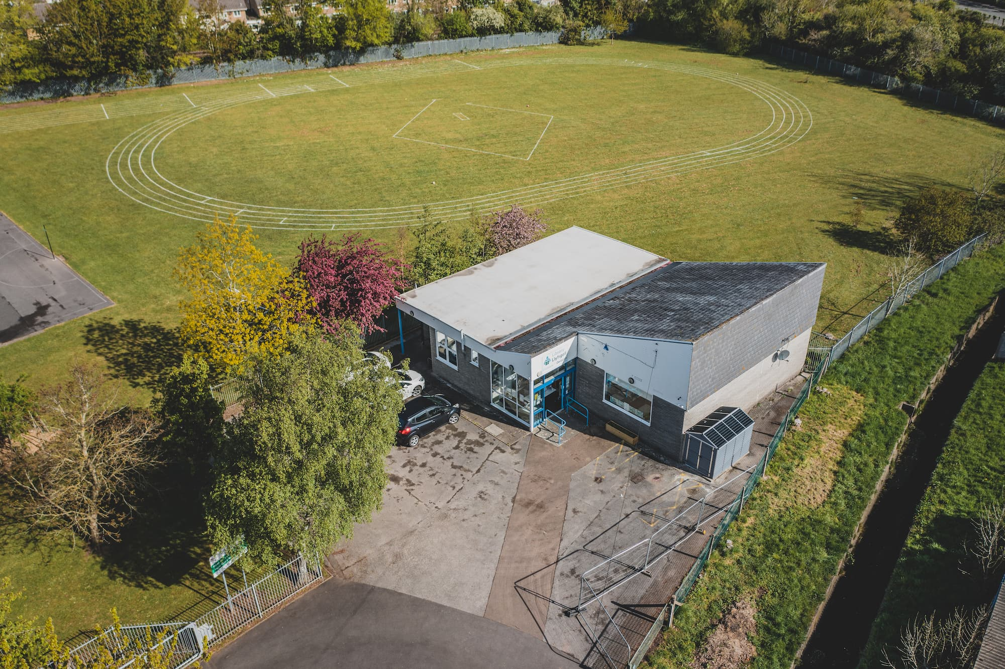 Arial view of Dinas Library. It's a modern, angular building next to trees and a big running field.