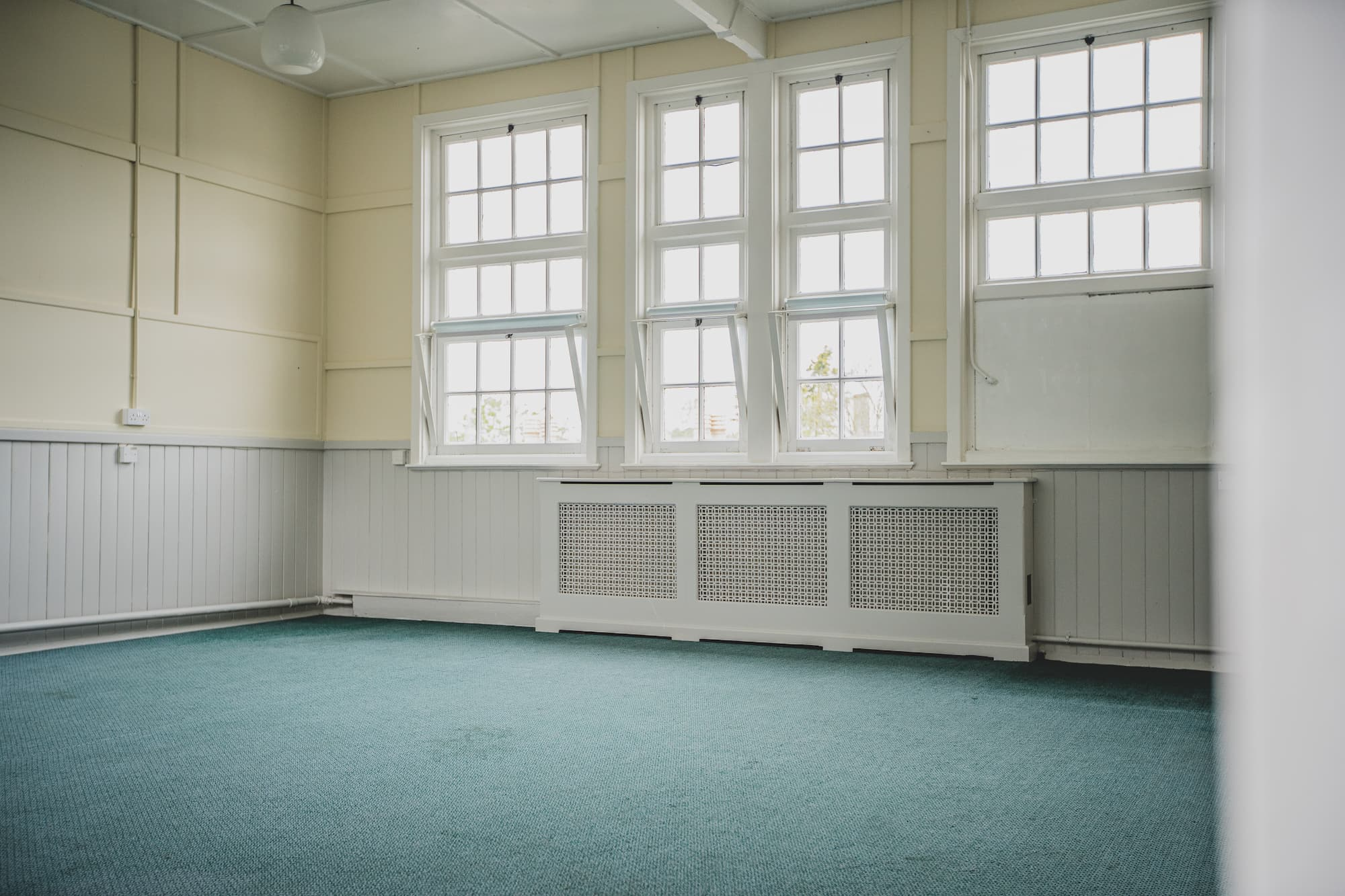 A view of the set of large windows in the work room with a long, covered radiator underneath them.