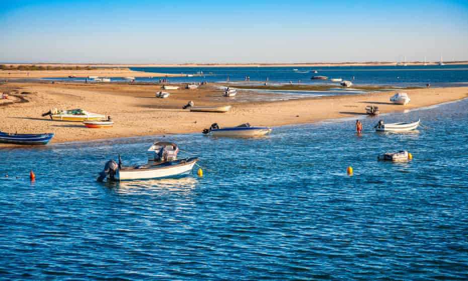 Fishing boats on a sandy anchorage.