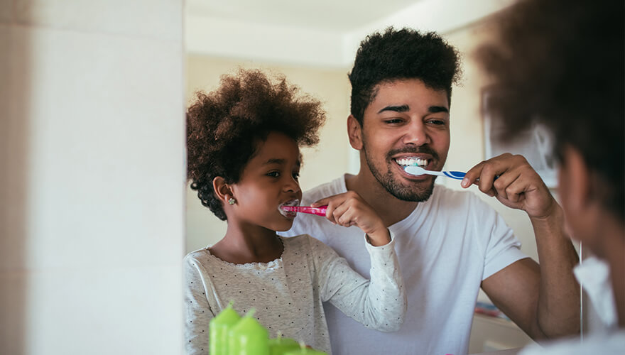 Father and daughter brushing their teeth together in front of a mirror