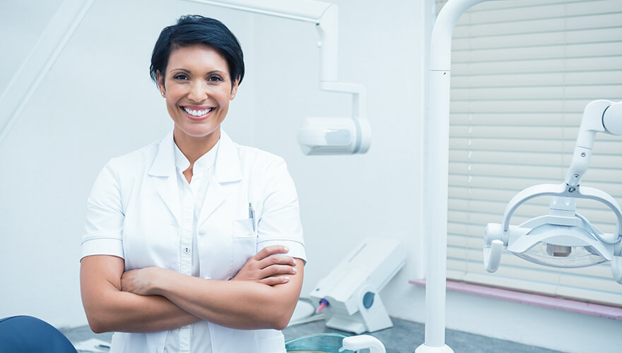 Smiling dentist standing in front of a dental chair