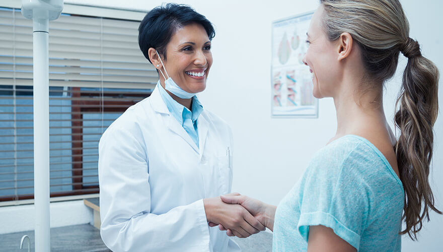 Dentist and patient shaking hands in the treatment room and smiling