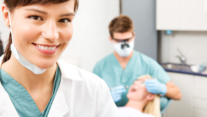 Closeup of a female dentist smiling while a male dentist is performing a dental filling on a patient
