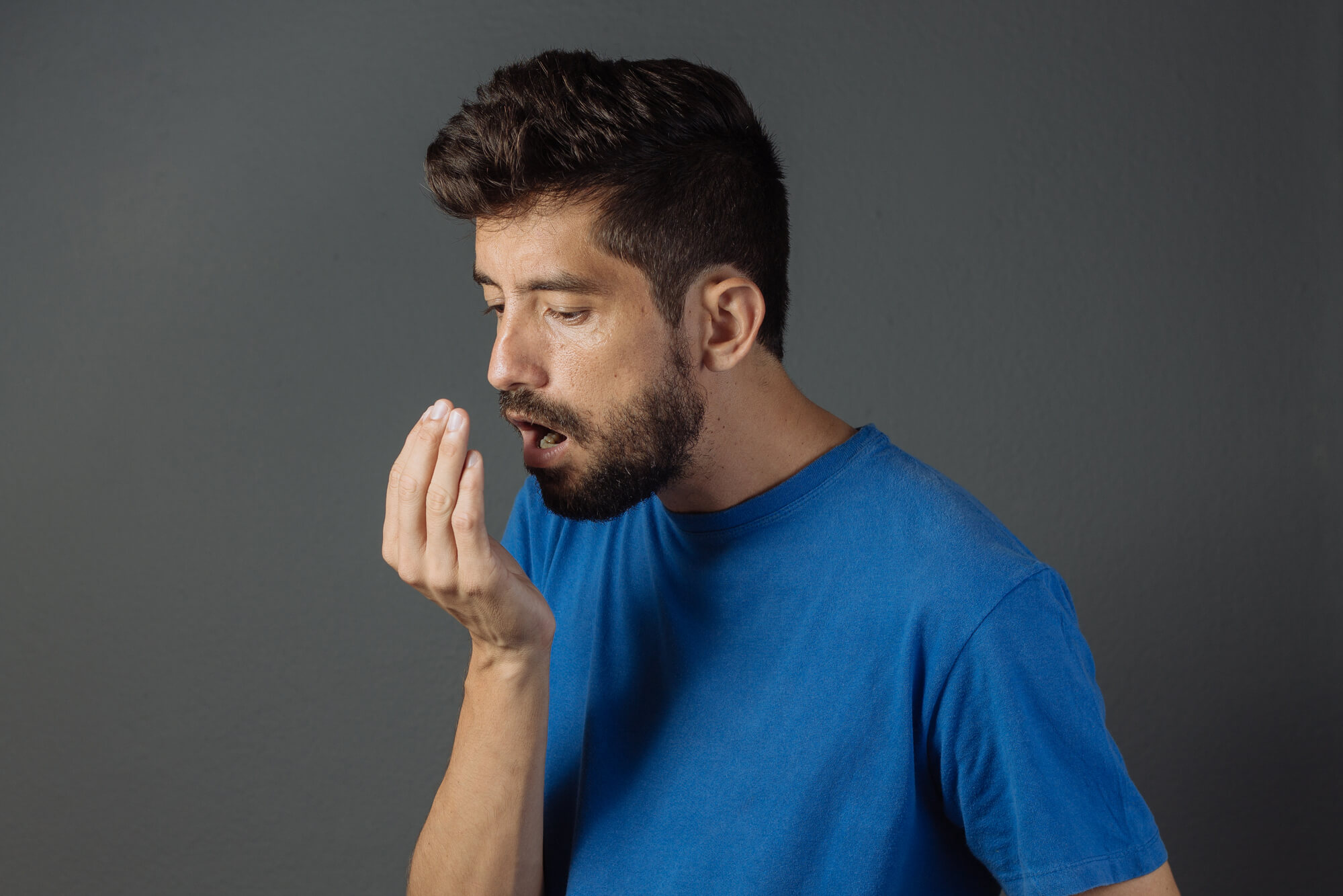 Man smelling his breath after a teeth cleaning inmarysville