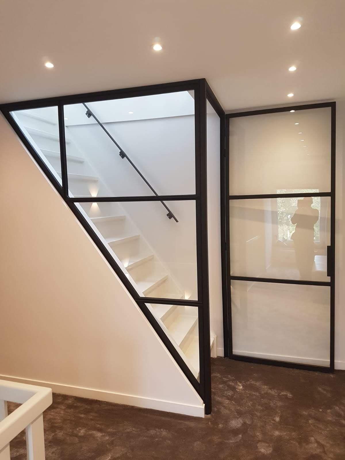 Stalen deur geplaatst in trappenhuis met glad stucwerk