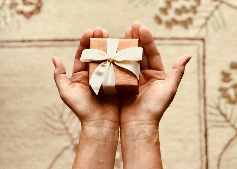 Photo of a person holding a small box with a bow in their palms for PolicyMe's article on legacy gifts