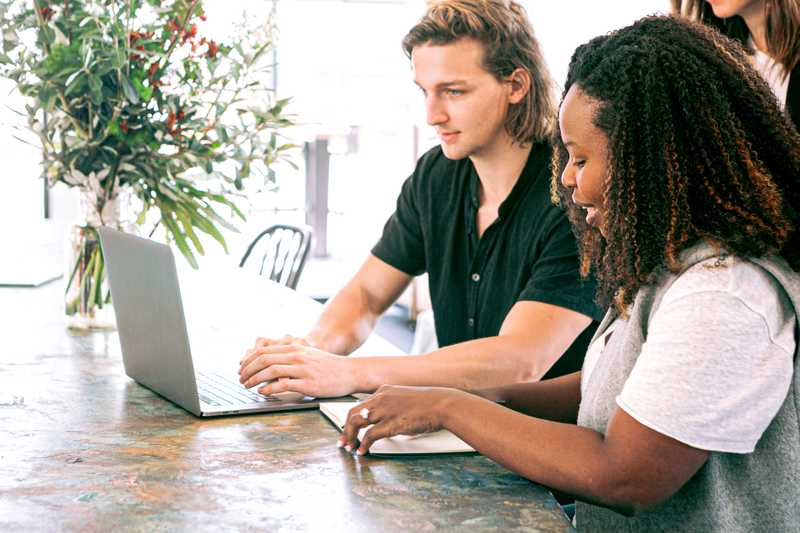 photo of a young man and woman sitting at a table on their laptops for PolicyMe's article on life insurance for millennials