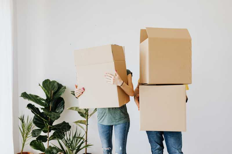 Photo of a man and a woman standing side by side while holding moving boxes for PolicyMe's article on buying a home