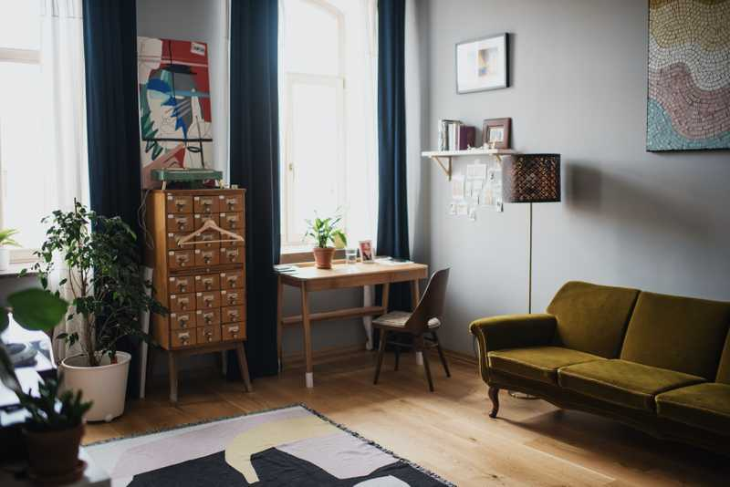 Photo of a living room with a green couch and a wooden desk for Policyme's article on buying a house in Canada