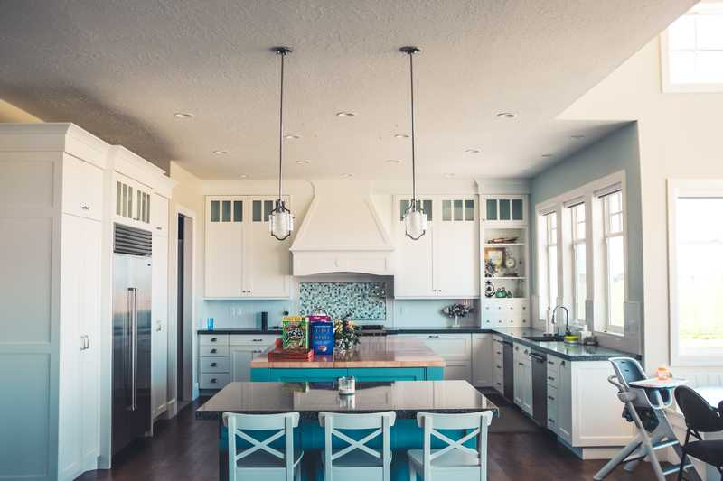 a white kitchen with turquois accents in a family home