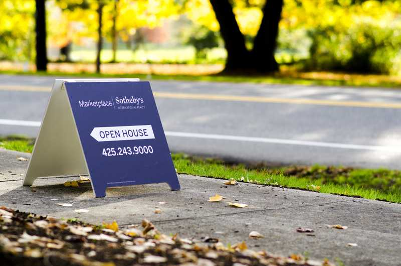 navy blue sign on a sidewalk advertising an open house