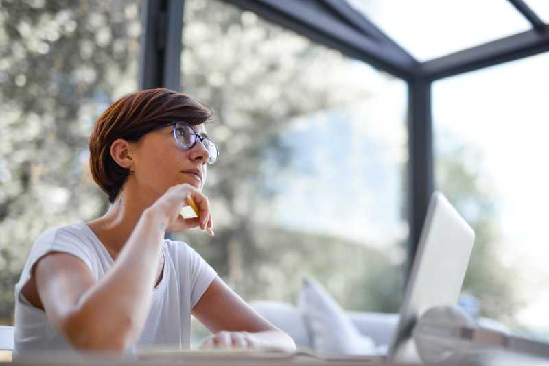 a woman is thinking while working on her laptop for PolicyMe's article on term life insurance