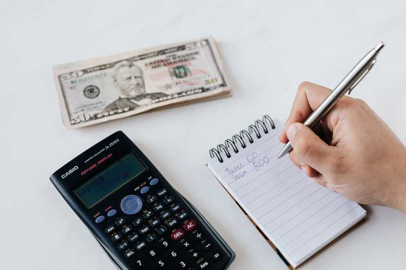 A person budgets their cash using a notepad, and calculator for PolicyMe's article on financial planning for Canadians