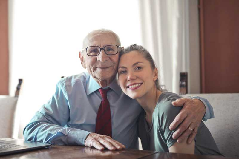 an elderly father and his grown-up daughter embrace each other