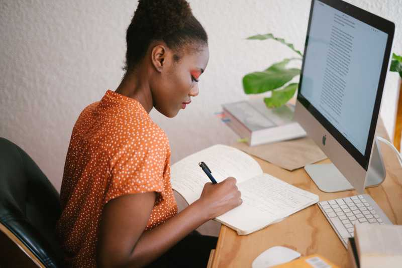 A photo of a woman writing in a notebook at a desk for PolicyMe's article on how much of your paycheck should you save