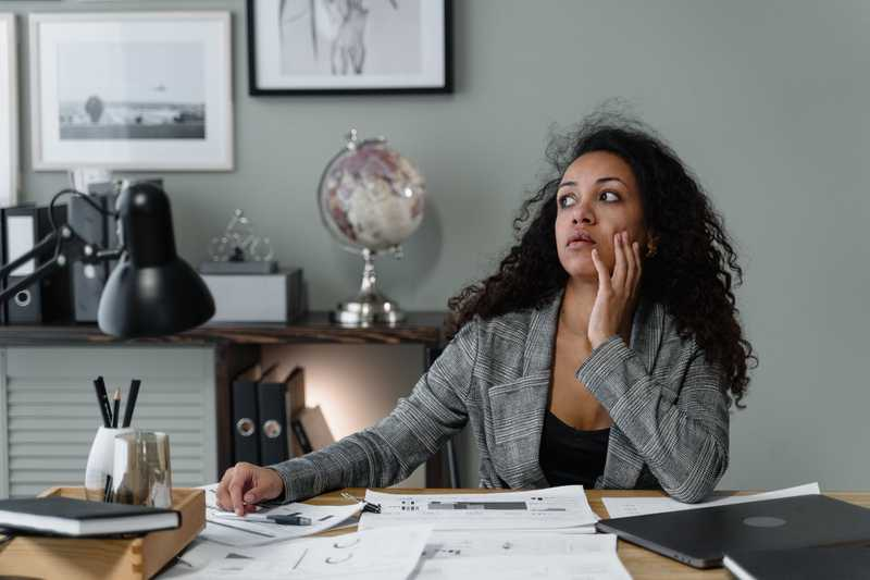 """photo of a woman thinking while sitting at a desk for PolicyMe's article on """"is life insurance taxable?"""""""